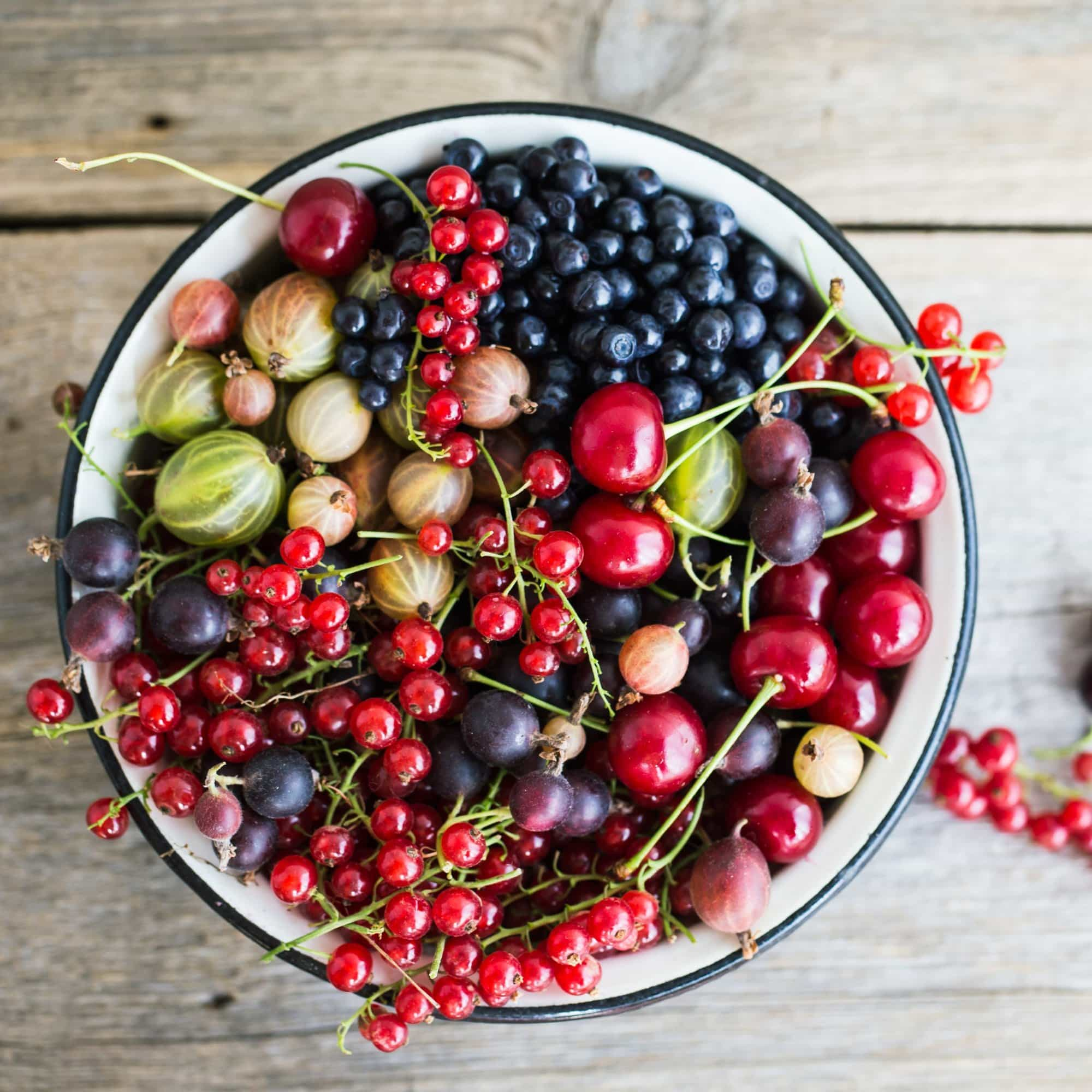 Different fresh berries in a pot on the wooden background