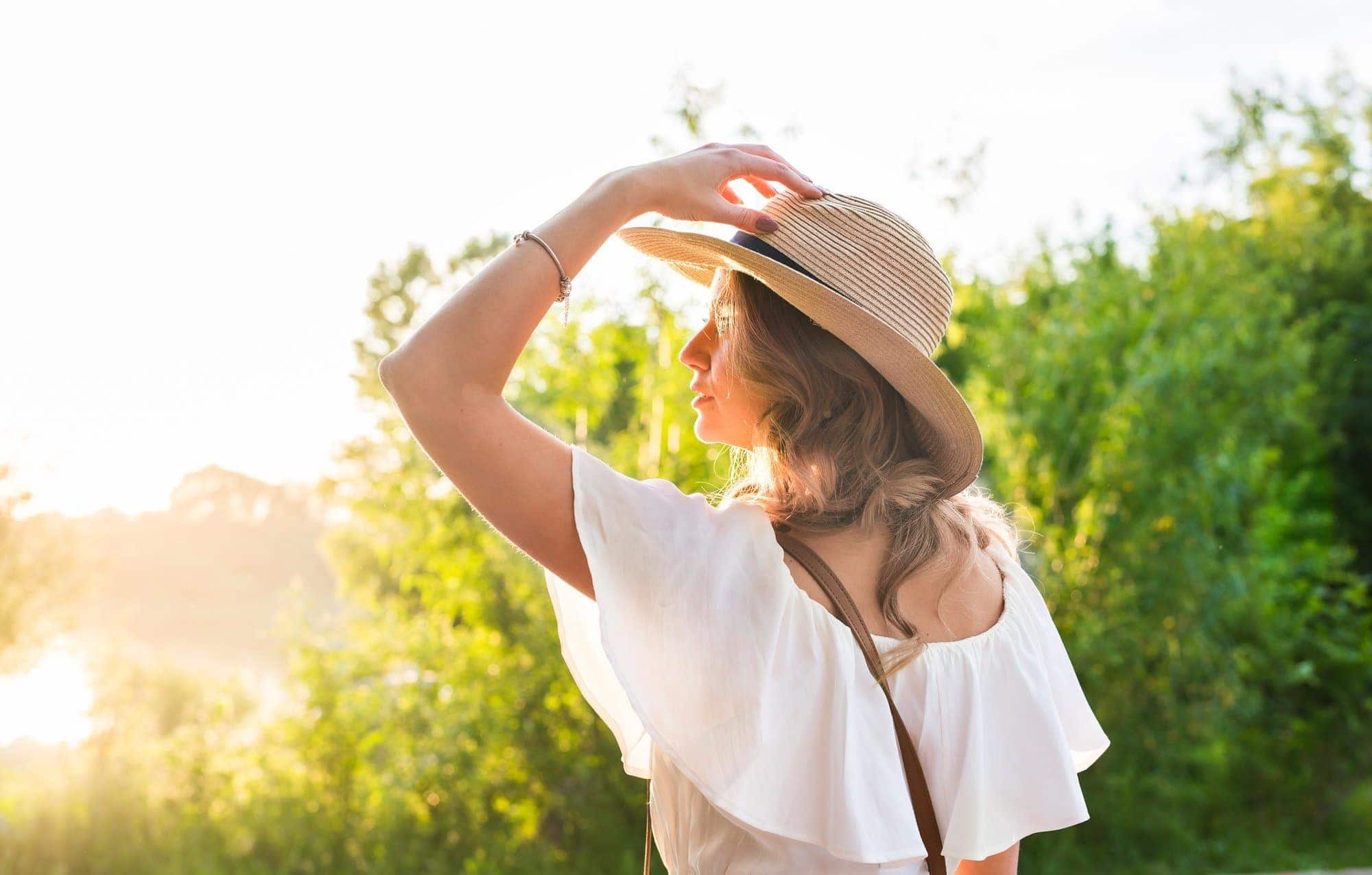 Woman in big straw hat enjoyed with summer sun