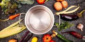Various organic vegetables ingredients around empty cooking pot